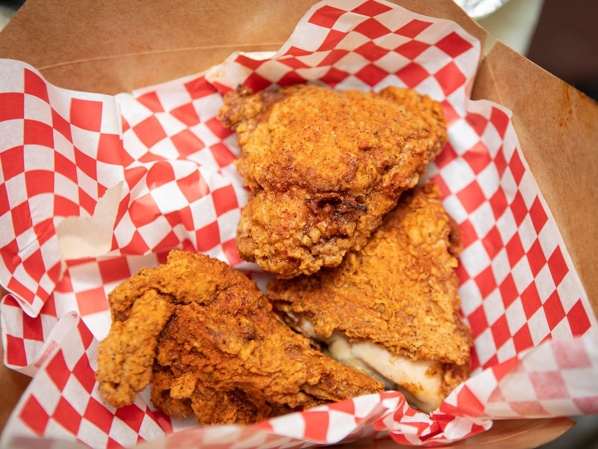 Three pieces of golden, crusty fried chicken sit in a paper to-go box lined with red and white checkered paper