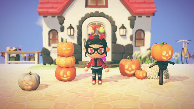 A horned Animal Crossing character ominously stares at the camera while surrounded by pumpkin furnishings