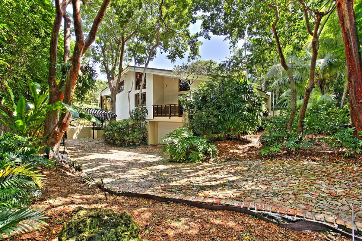The lush landscaping outside a white Frank Lloyd Wright-inspired home in Coconut Grove.