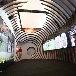 Spencer Quarles, right, watches a video in a football shaped room at the grand opening of the new Spence and Cleone Eccles Football Center at the University of Utah in Salt Lake City on Thursday, Aug. 15, 2013.