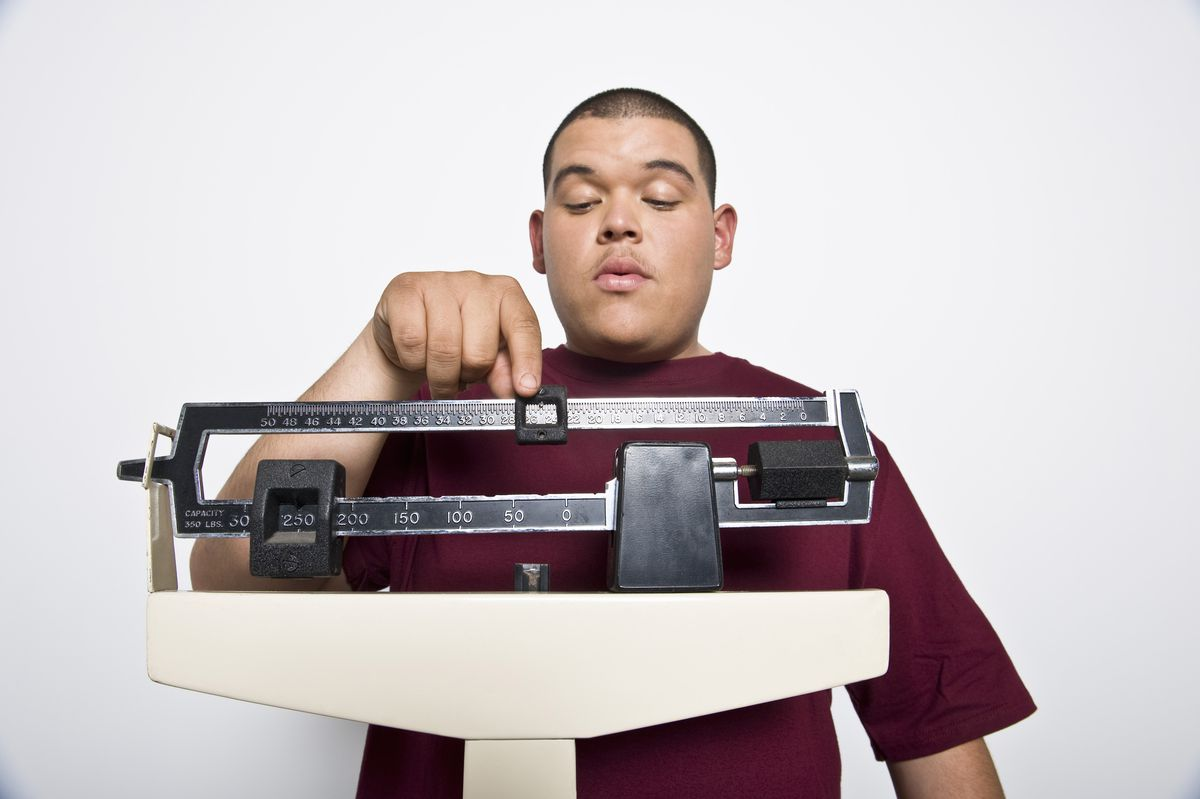 Man weighing self with scale