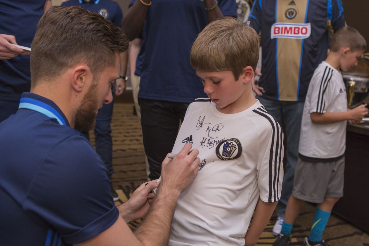 A Reading United player signs a young fan's jersey at the team's annual meet and greet event.