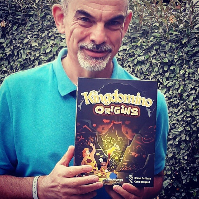 A man with a salt-and-pepper goatee stands in front of a hedge. In his hands a copy of Kingdomino Origins, with a big volcano on the front.