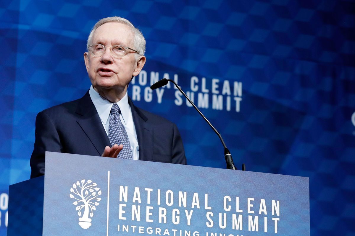 "Former Senate majority leader Harry Reid speaking from behind a podium labeled ""National Clean Energy Summit."""