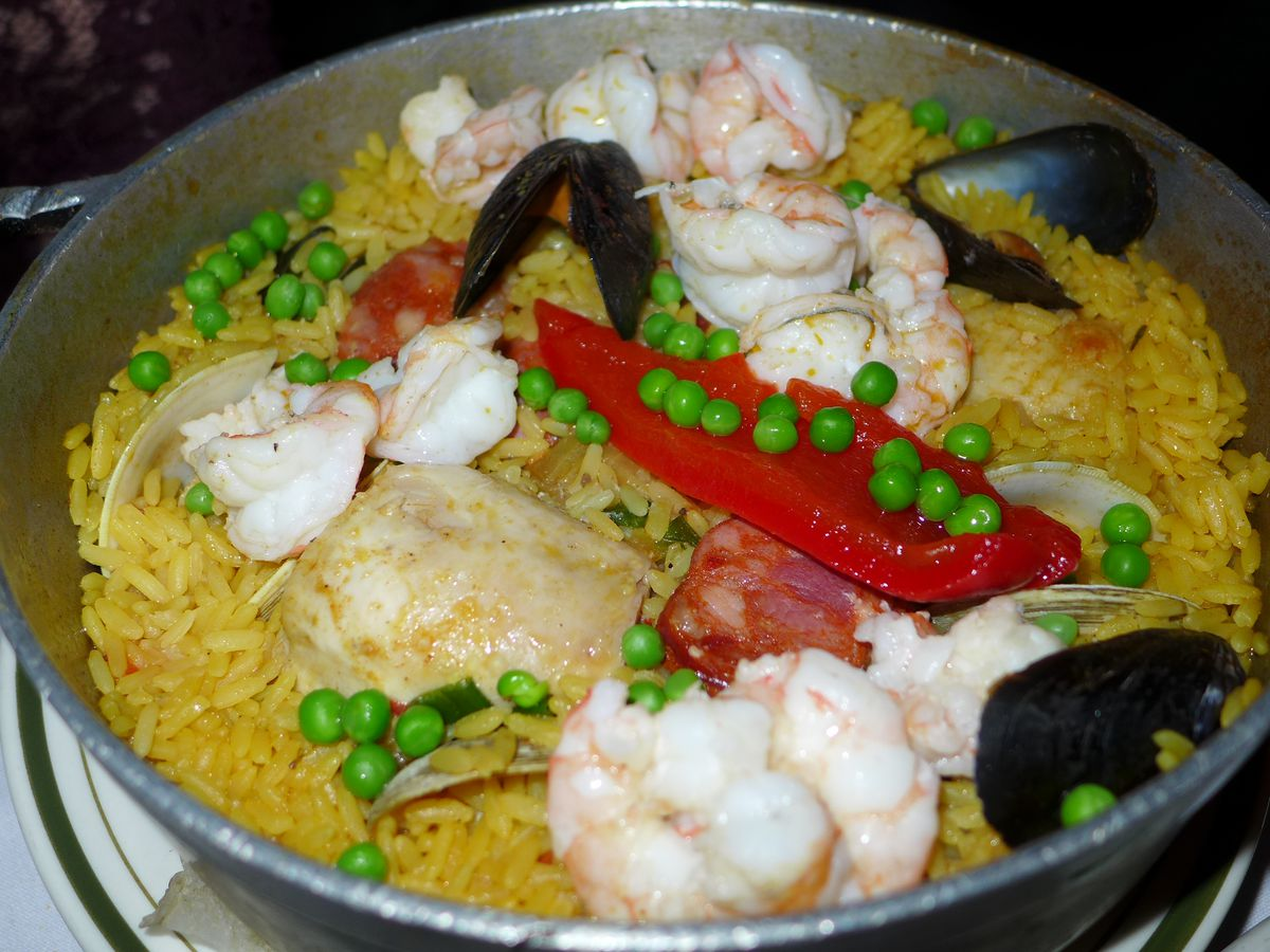 An aluminum pot with seafood, yellow rice, and bright red peppers.
