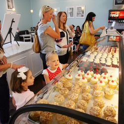 Kathy Sullivan, left, looks to buy cupcakes for her daughter Amanda, front left, and friend Addi Cutler look at all the cupcakes on display at The Sweet Tooth Fairy Gourmet Bake shop Monday, April 9, 2012. The company won the Food Network's Cupcake Wars.