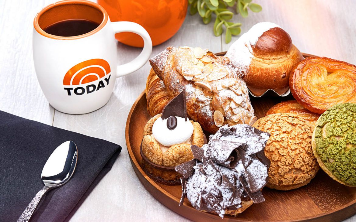 A tray of pastries and a branded TODAY mug fill out a breakfast spread