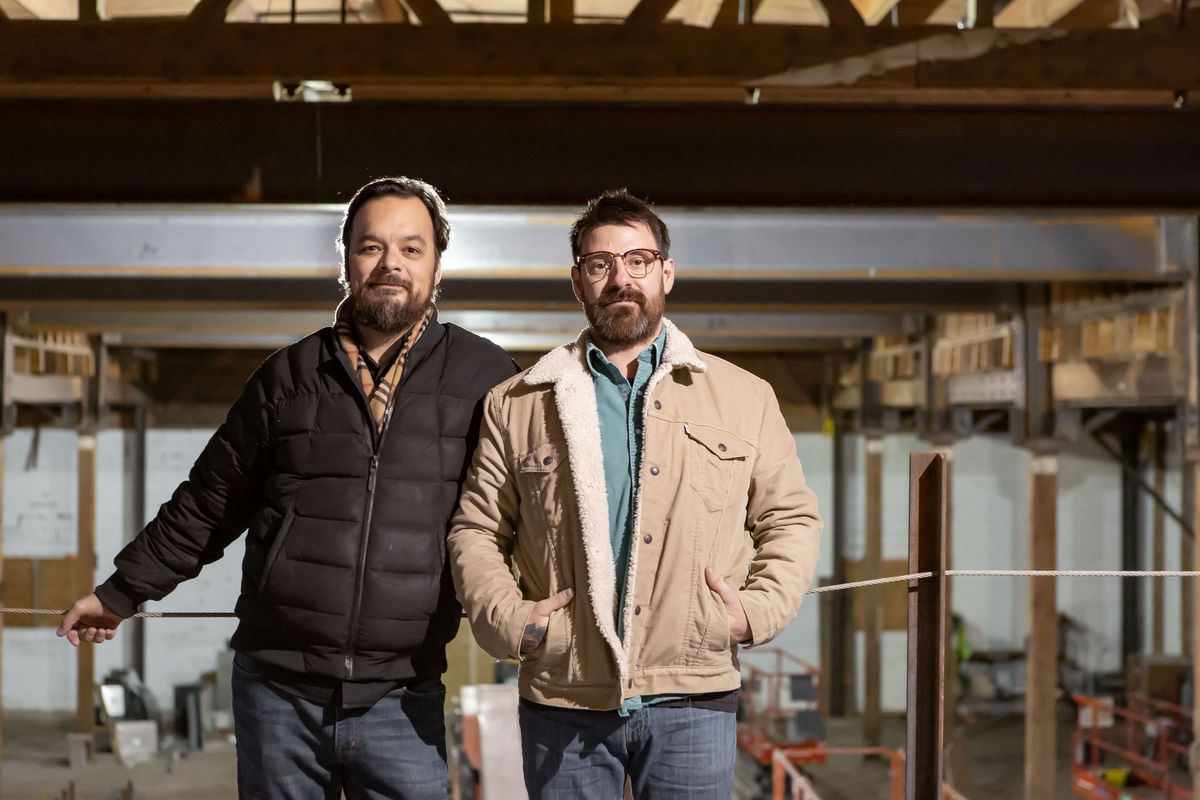 Jesse Held and Jeff Erkkila stand together, not smiling, in winter jackets on the site of their new distillery