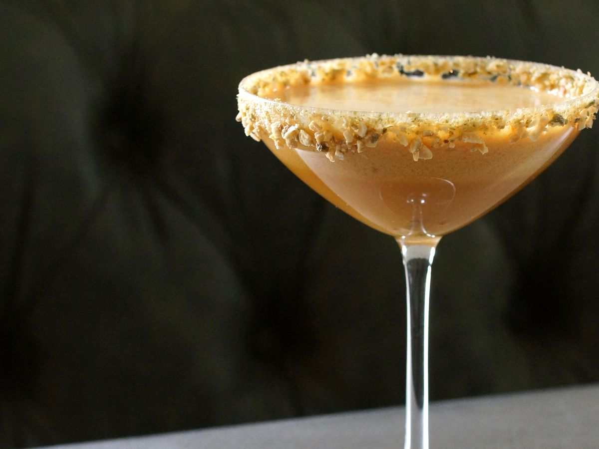 A brown cocktail in a martini glass.