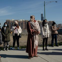 People watch as the Via Crucis procession passes by in Pilsen, Friday morning, April 2, 2021. The annual Via Crucis is a Good Friday tradition that reenacts the Stations of the Cross, a Catholic devotion that recounts Jesus' passion and death.