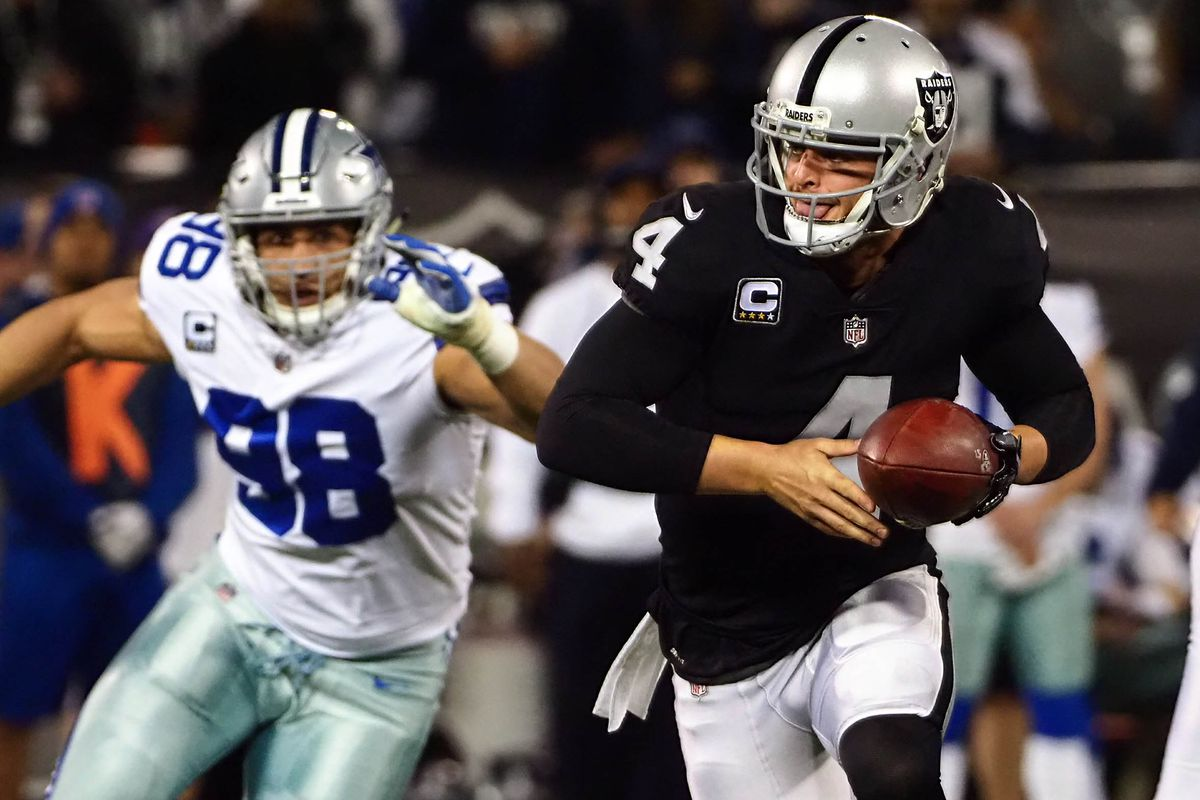 Oakland Raiders quarterback Derek Carr looks to hand off the ball ahead of Dallas Cowboys defensive end Tyrone Crawford during the first quarter at Oakland Coliseum.