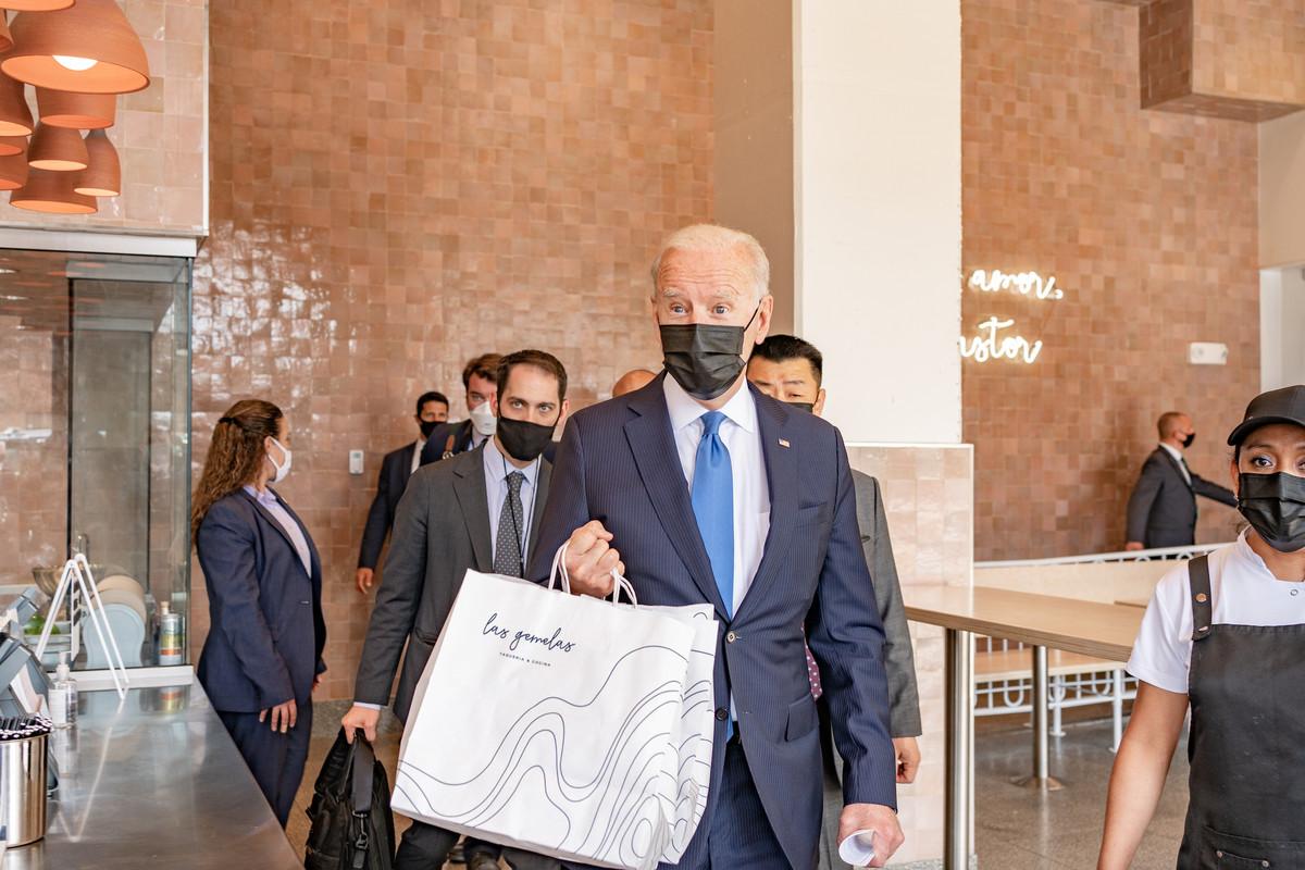 President Joe Biden wears a mask and walks through Taqueria las Gemelas with a white takeout bag