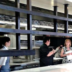 Jose Garces and interior designer Marguerite Rodgers discuss the space as chef Natalie Maronski, the kitchen's second-in-command, looks on.