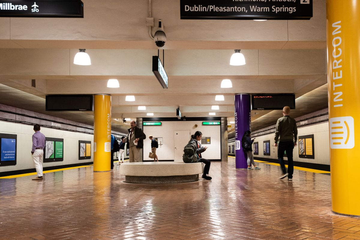A subway platform in San Francisco, with the support pillars wrapped in yellow ad posters.