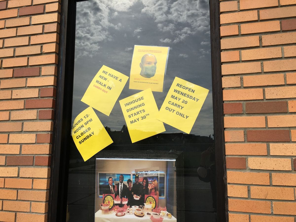 Yellow signs on the window at Brush Street Bar &  Grille tell customers to wear masks and erroneously state that in-house dining starts on May 30.