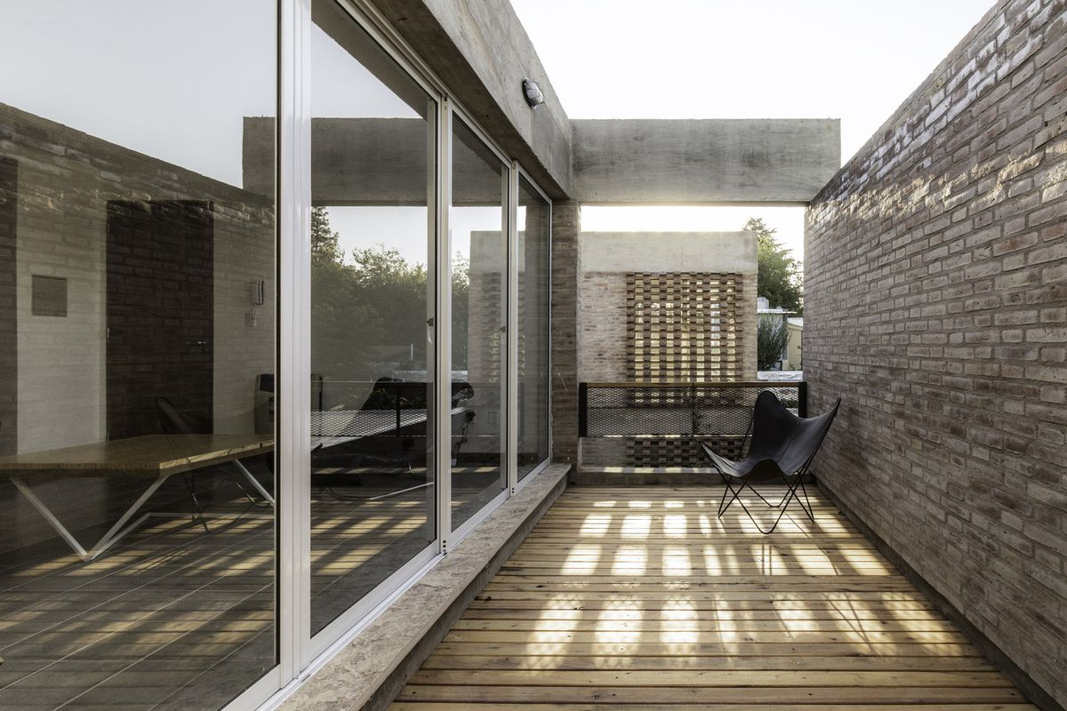 Terrace with wood plank floors and brick wall.