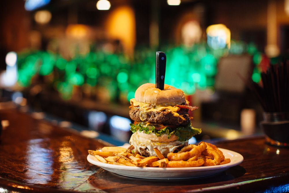 A burger with two thick patties and three buns, is held together with a steak knife and surrounded by french fries on a plate.