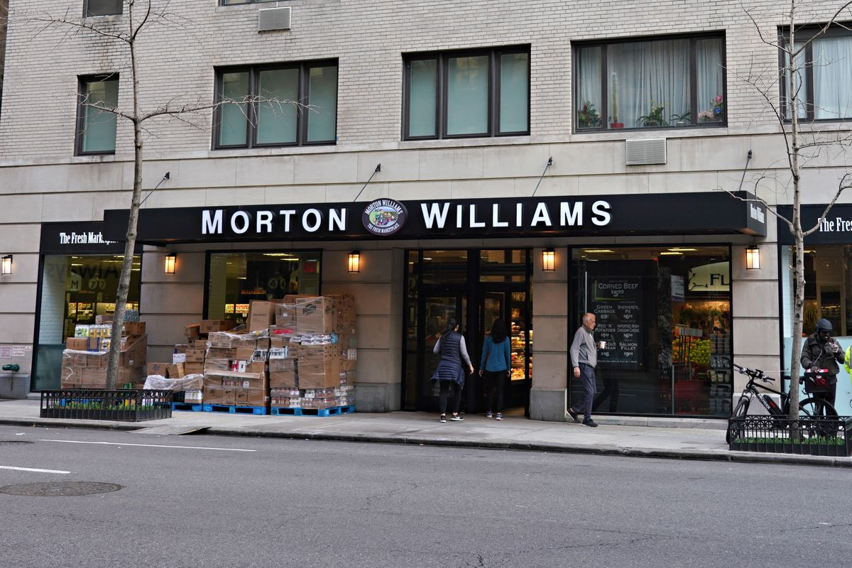 Workers can be seen moving groceries outside of a Morton Williams store
