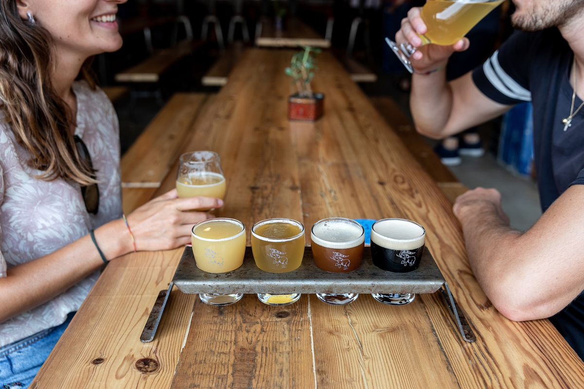 A series of beers in a metal tasting display shown from light to dark surrounded by two people sitting at a table.