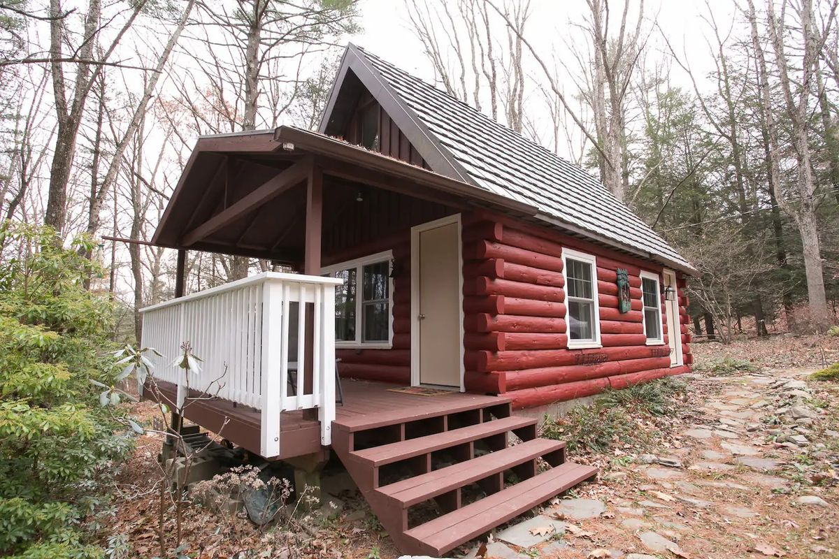 A cabin in Barrett Township. The facade has red logs and a sloped roof. The cabin is surrounded by trees.