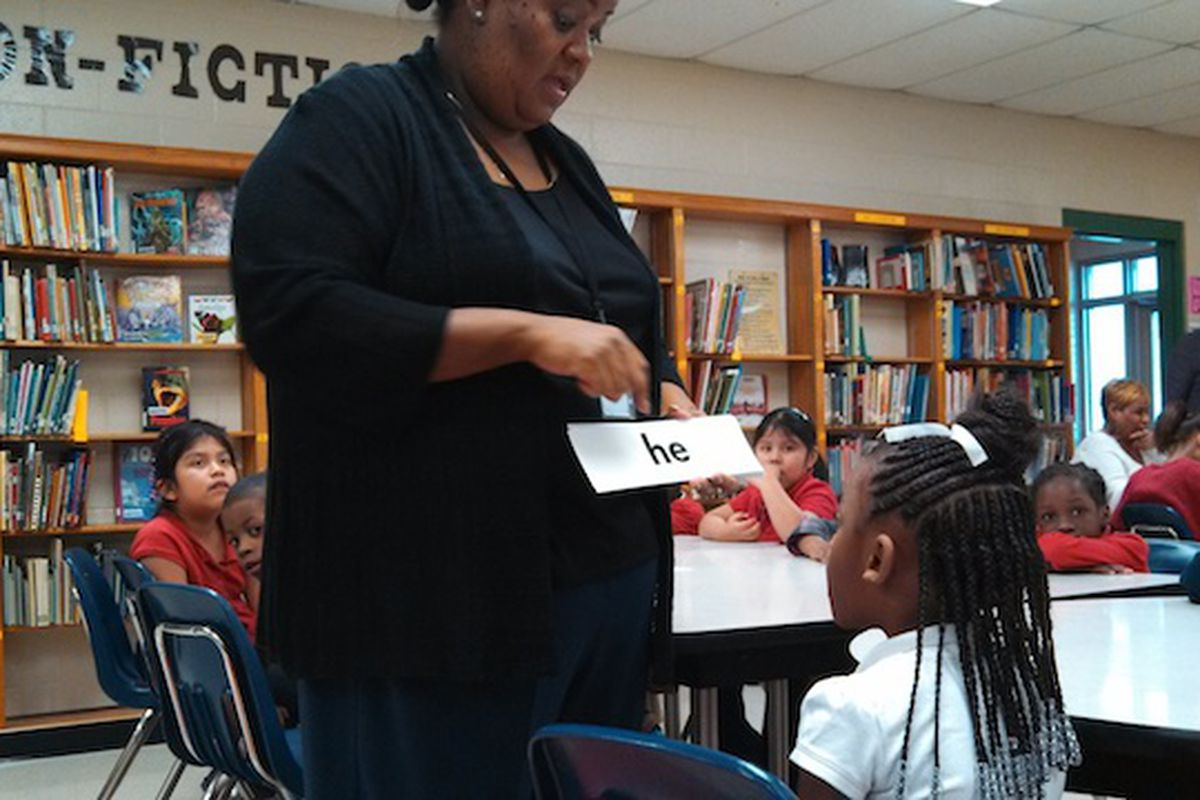Sharpe Elementary reading interventionist Valencia Ealy works one-on-one with a student on vocabulary words last year in Memphis. Shelby County Schools has started its own program to address lagging literacy scores.