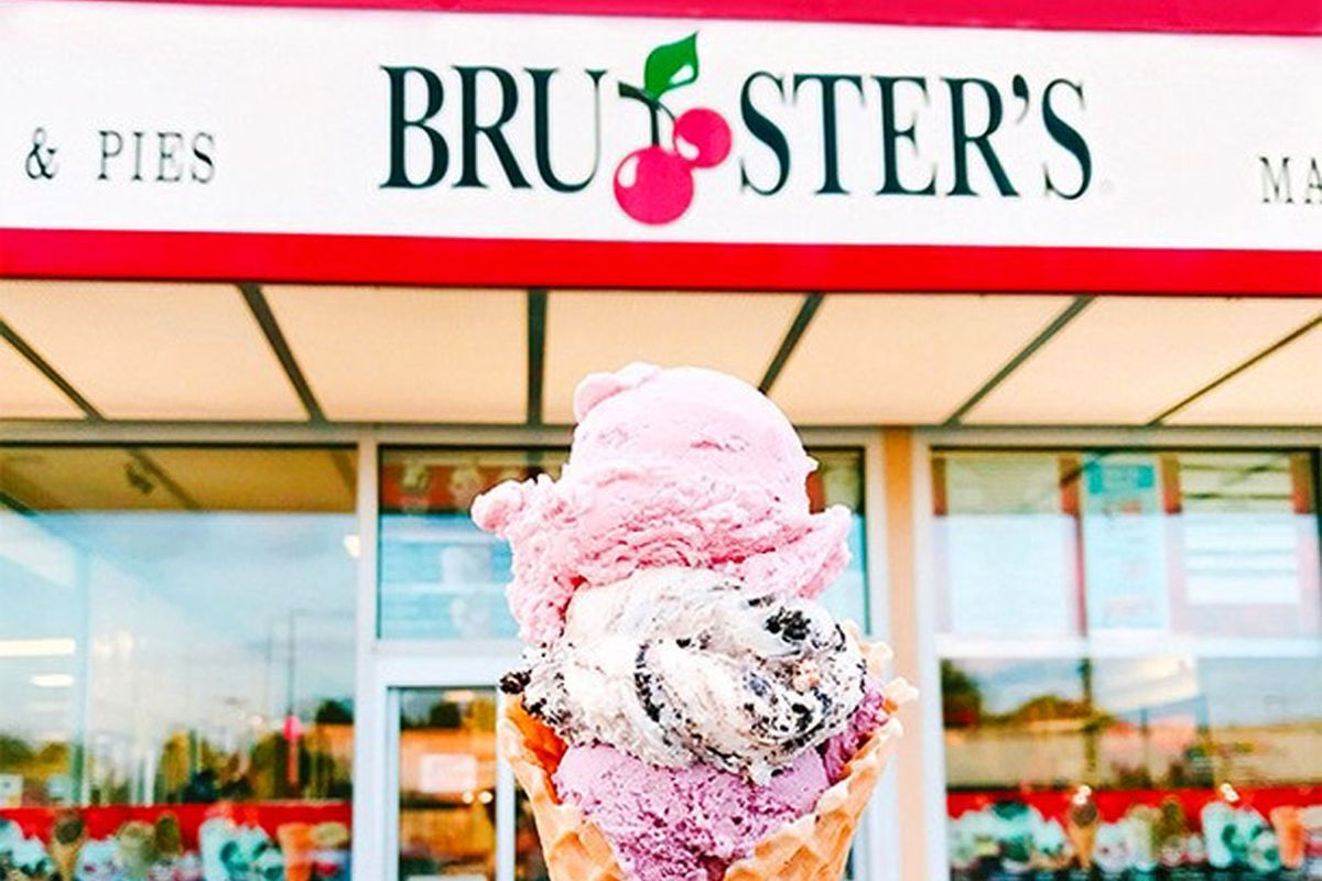 A waffle cone with three scoops of store-made ice cream, posed outside a Bruster's Real Ice Cream dessert shop.