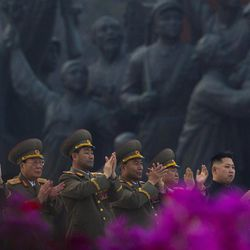 North Korean leader Kim Jong Un, far right, applauds with senior military officials as citizens wave flowers at an unveiling ceremony for statues of the late leaders Kim Il Sung and Kim Jong Il in Pyongyang, North Korea, Friday, April 13, 2012.