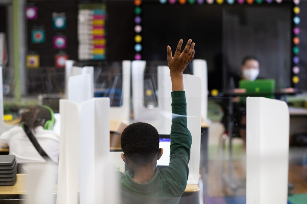 A fourth grade student raises his hand in class. The photo shows the back of the student's body with his hand in the air. The teacher is visible in the background of the photo, facing the camera. The teacher is wearing a face mask. The student's desk is surrounded by plastic dividers.