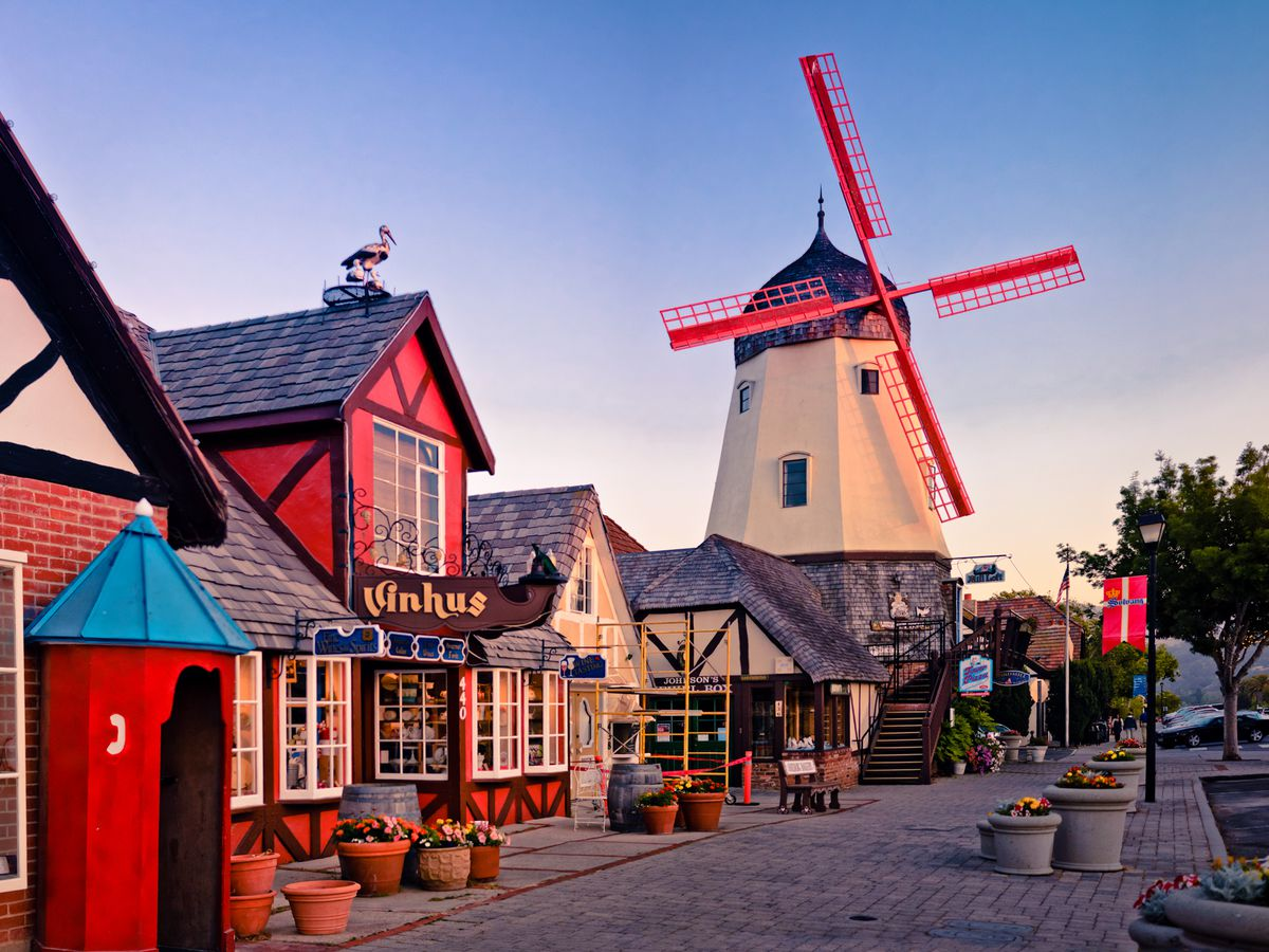 A street filled with buildings that have wood on the facades, in front of a large windmill painted red and white