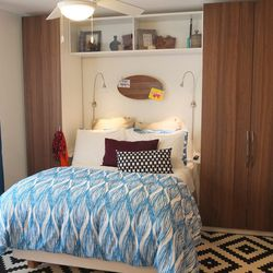 The tall storage units on each side of the bed are PAX units with STOCKHOLM doors. The lights above the bed are TIVED wall/clamp spotlights. And Mansaray's collection of art and souvenirs is on display in a GALANT wall cabinet above the bed.   <em>Spenc