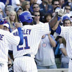 Chicago Cubs' Jake Fox is greeted at home plate by Milton Bradley, and Kosuke Fukudome after hitting a grand slam off New York Mets starting pitcher Bobby Parnell.