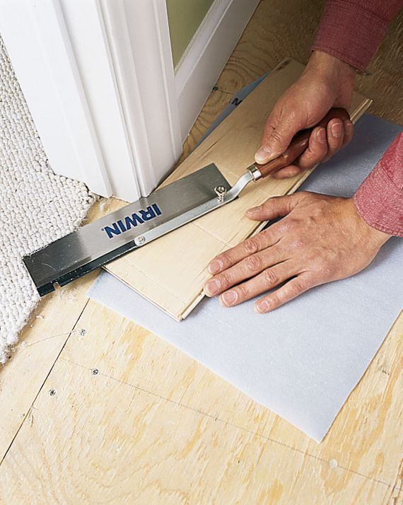 Man Trims Bottom Of Door Casing With Flush-Cut Dovetail Saw