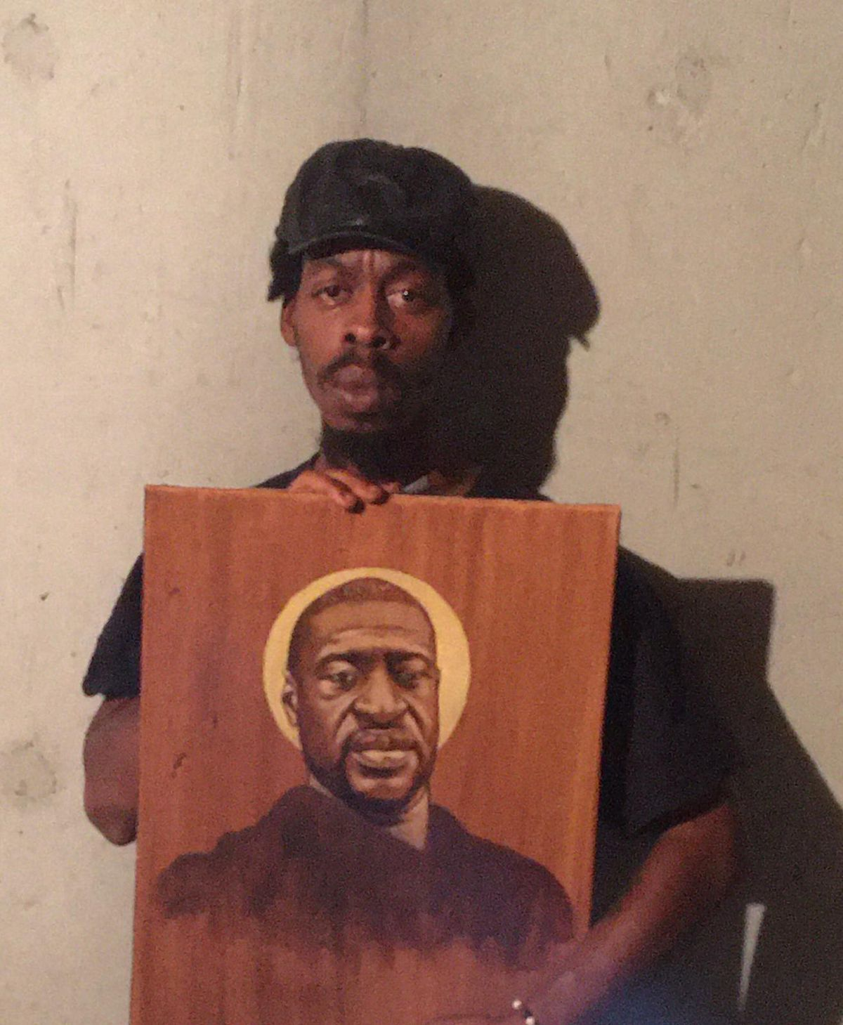 A Black man holds a painted portrait of George Floyd with a halo of light behind his head.