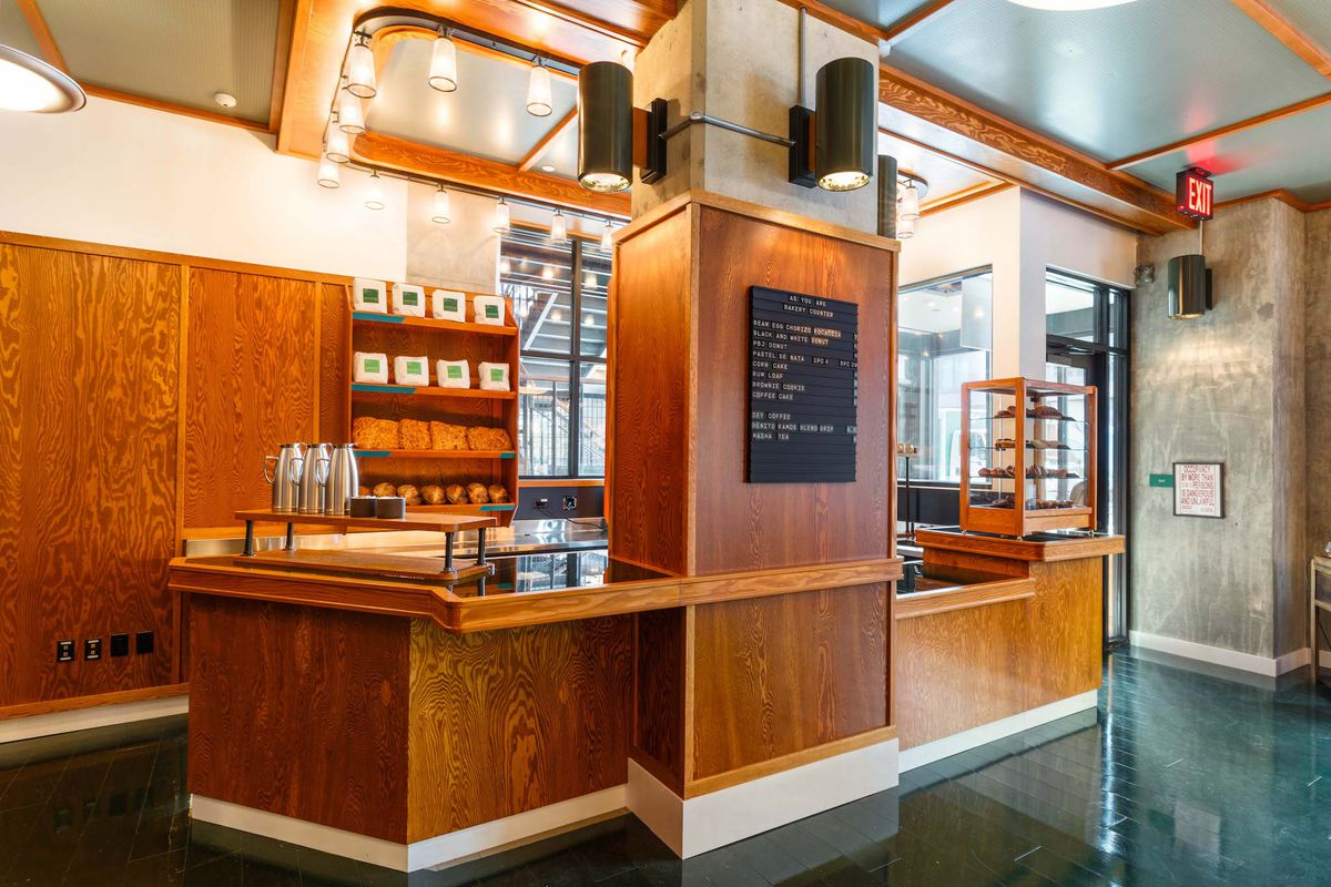 A wooden bakery counter with a black chalkboard, green marble floors, and shelves lined with bags of coffee.