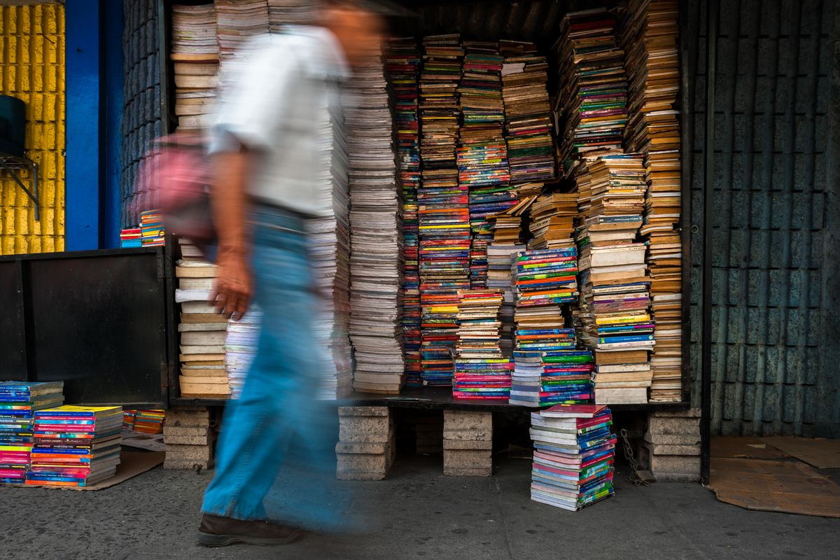 A man walking on a sidewalk past a display of books stacked as high as his head.