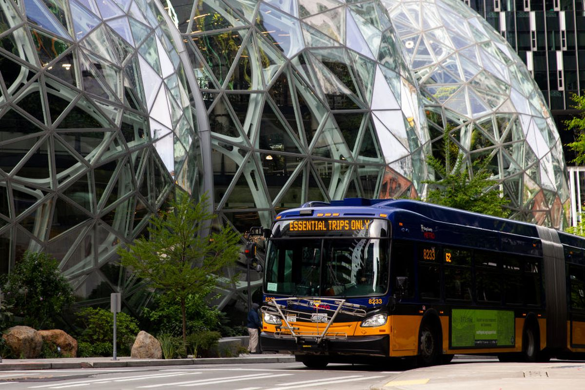 """A bus showing a sign that says """"Essential Trips Only"""" passes the Amazon Spheres in downtown Seattle."""