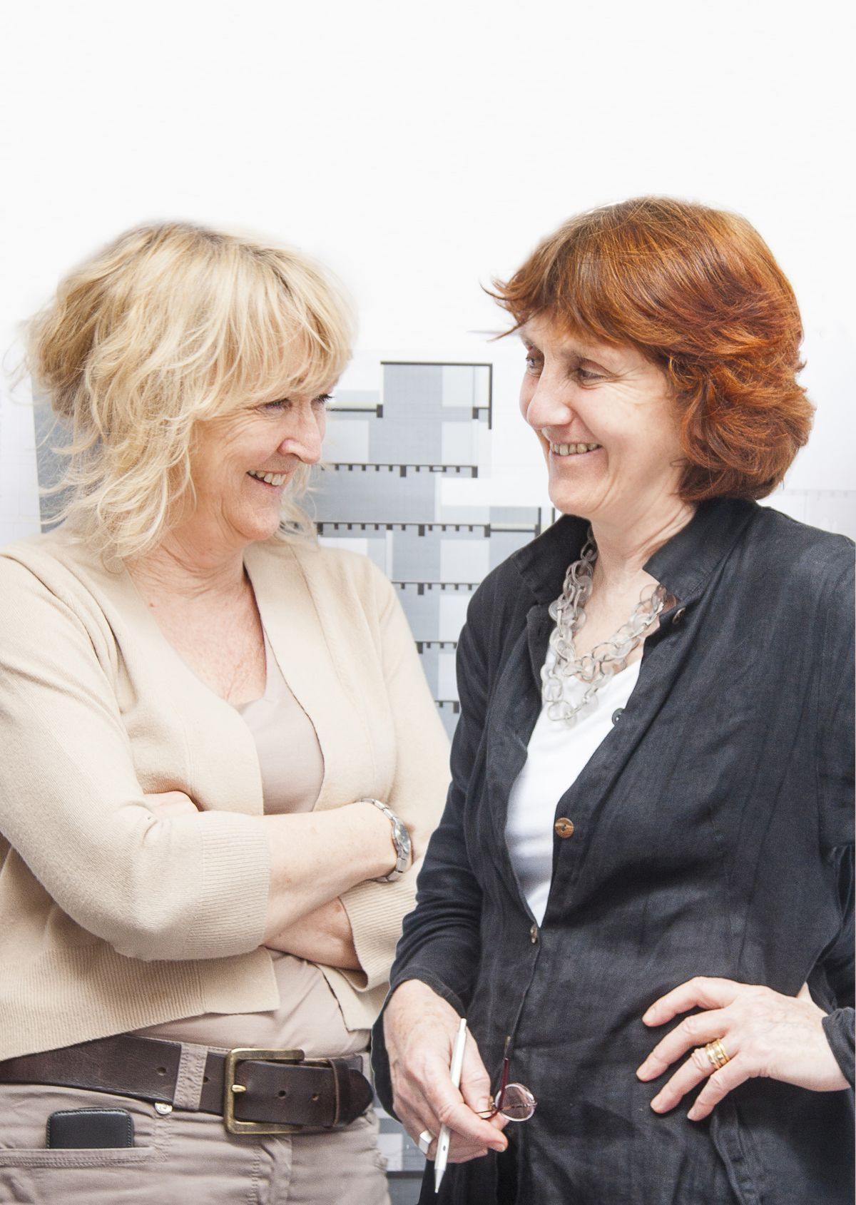 Two women facing each other in front of an architectural drawing.