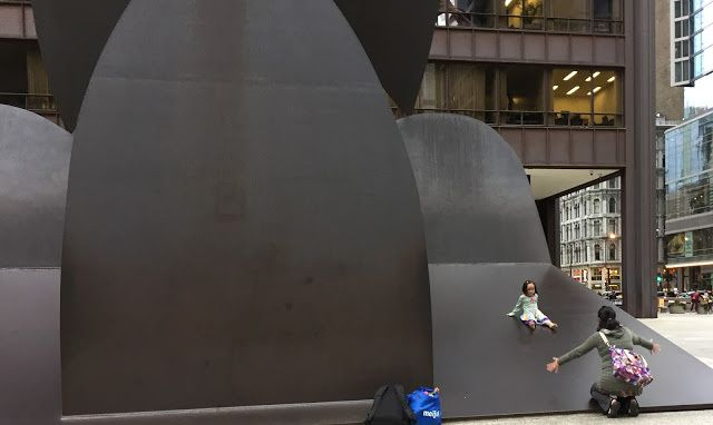 Maya Mulia encourages her daughter Skye, 3, to slide down the Picasso sculpture, which was unveiled 50 years ago — on Aug. 15, 1967. | Neil Steinberg / Sun-Times