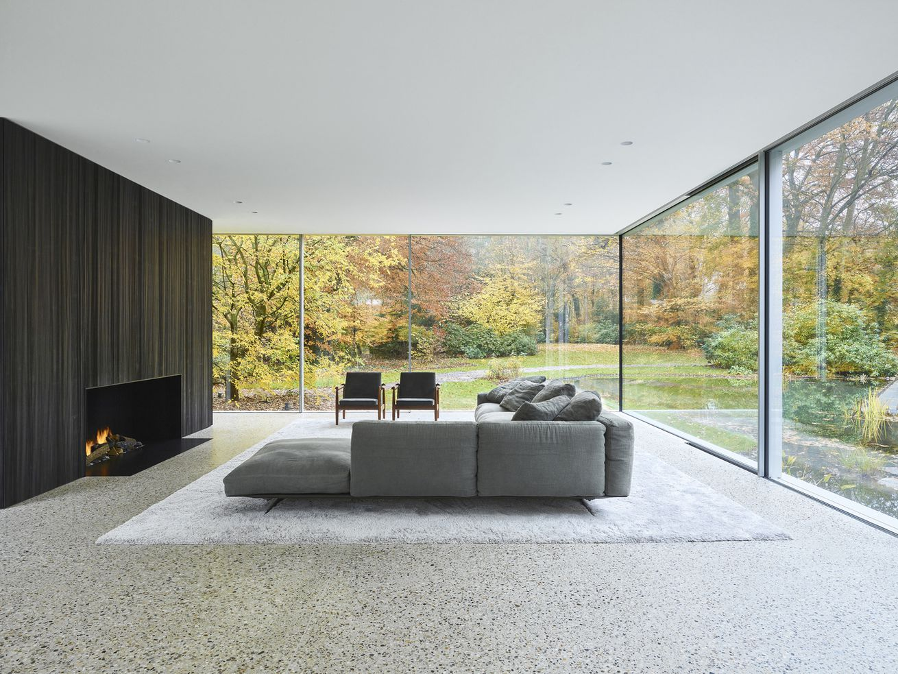 Living room with neutral colors and large windows showing trees going through foliage.