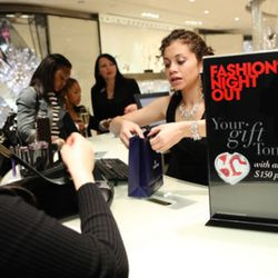 NEW YORK, SEPTEMBER 8: A guest makes a purchase at Fashion's Night Out at Swarovski on September 8, 2011 in New York City. (Photo by Brendan Hoffman/Getty Images for Swarovski)