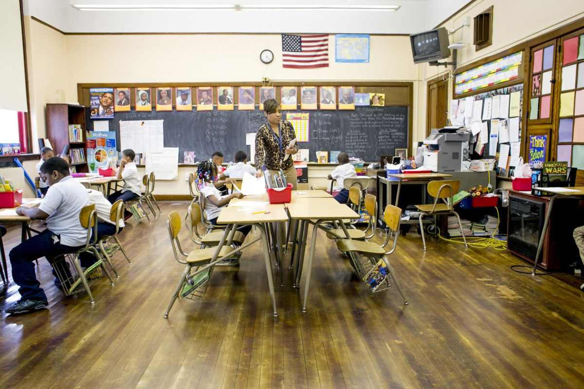 A teacher works with her elementary school students while they complete an assignment at their desks.