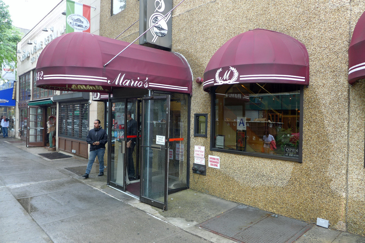 The exterior of a restaurant with a rounded red awning that reads Mario's