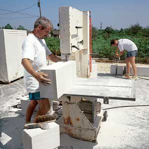 <p>Builder Mike Havinkin runs an AAC block through a band saw, a woodworking tool. This particular block will be used in a leveling course, the first row of AAC on top of a foundation. But first, Havinkin cuts a notch to allow for a threaded-steel reinforcing rod.</p>