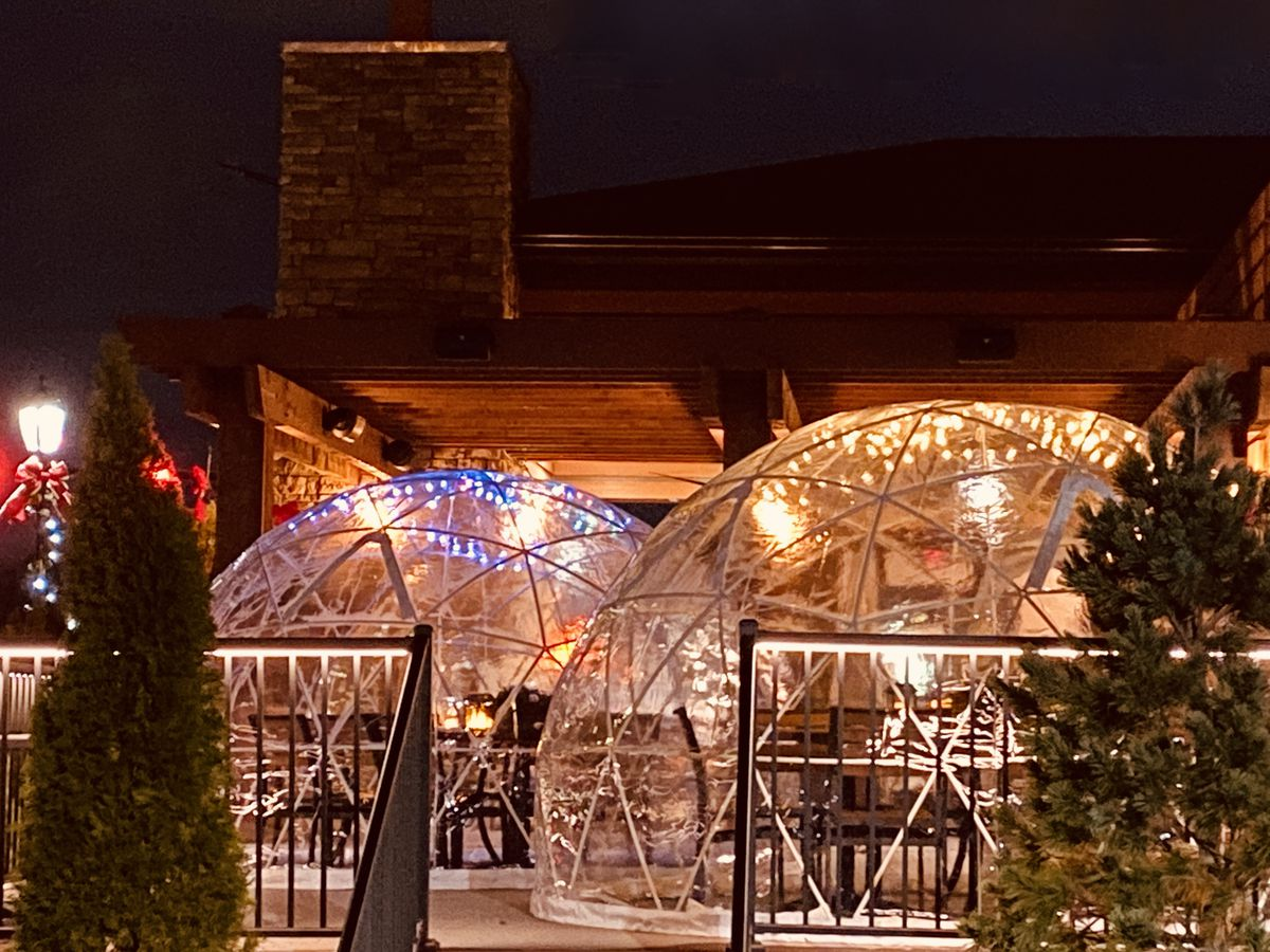 Outdoor dining igloos, lit by string lights, on a darkened patio beside a few small trees