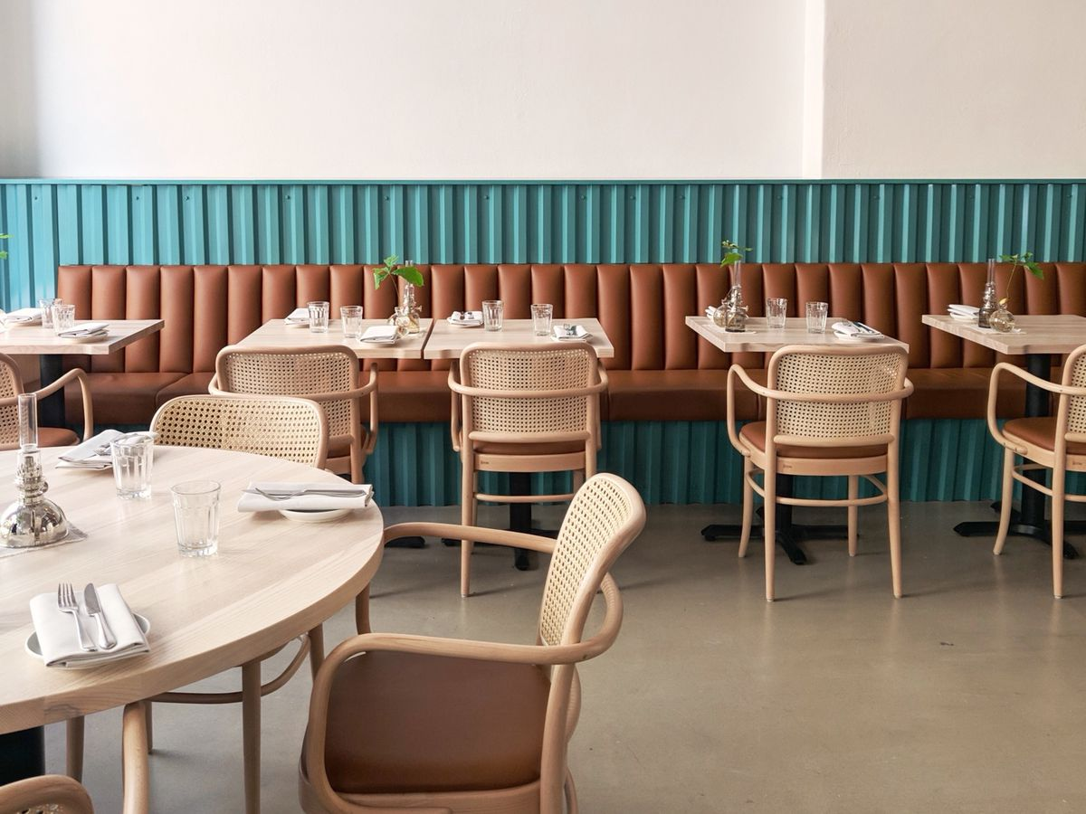 A brown leather banquet in front of teal paneling in a light, airy dining room, with four and two-top tables, curved patio-esque chairs and table settings