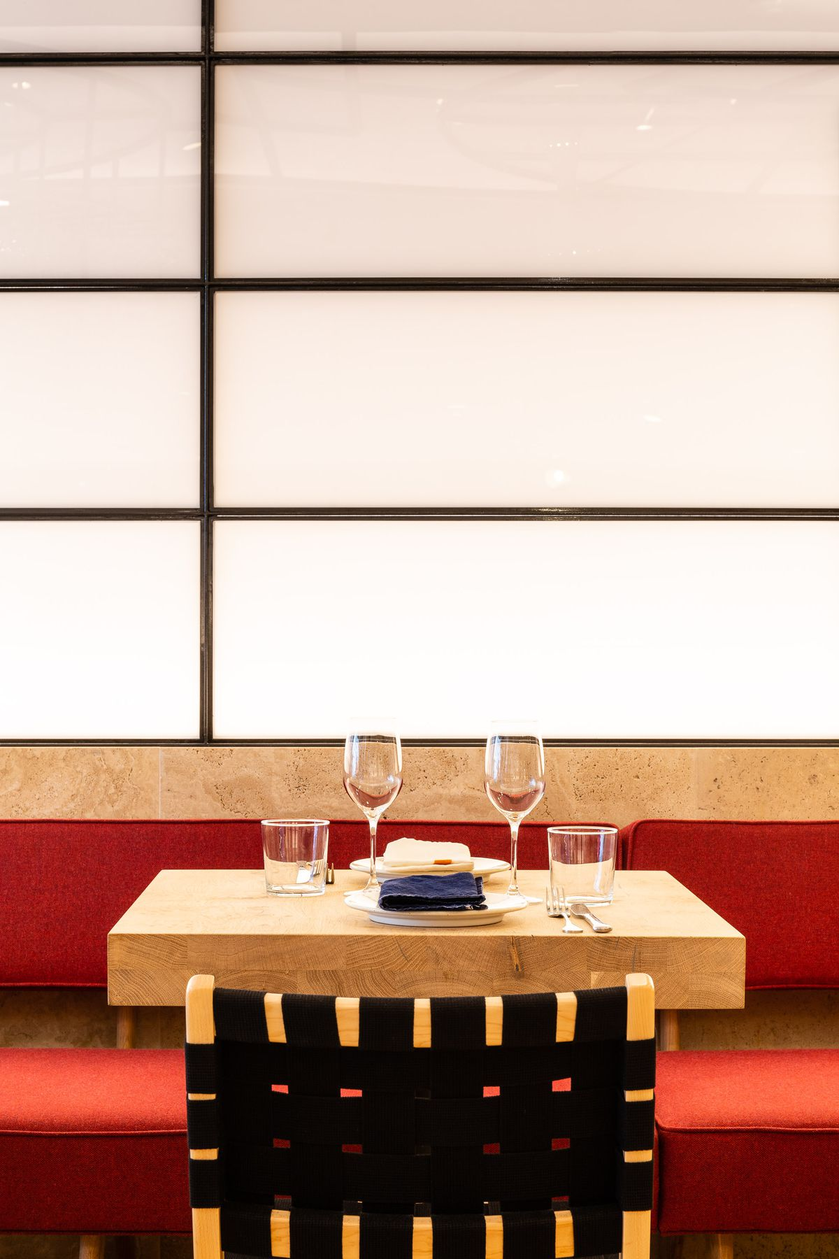 A table set with wineglasses and a red banquette at Yottam Ottolenghi's new London restaurant, Rovi