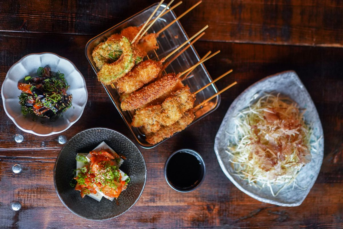 A top-down view of various Japanese deep-fried skewers and rice dishes from Taku.