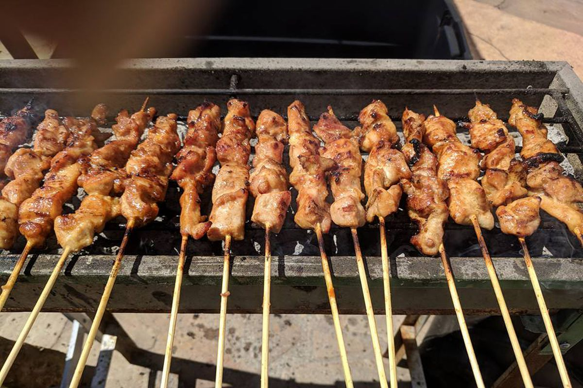 Grilling chicken skewers at Sate Texas