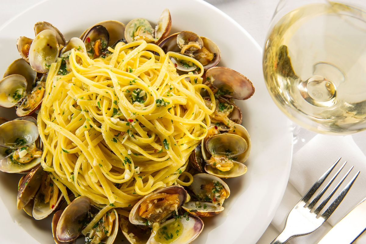 Pasta with clams on a white plate with white wine on the side.