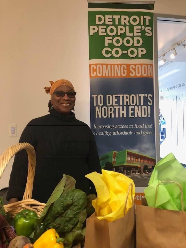 A woman smiles behind bags of produce next to a sign advertising the Detroit People's Food Coop.